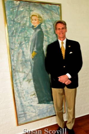 9. J.B. Kelly paused for a photo with Grace Kelly's portrait.