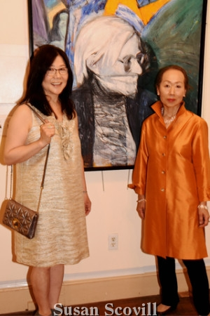 """3. Gee Shin and Tomoko Torii pose with a Richard Ranck painting called """"Gag Andy"""""""