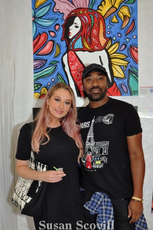 5. Isabelle Staub chatted with artist Aloysius McIlwaine about his work titled ''Colorful Woman in a Dress Canvas''.
