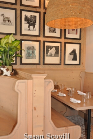 "The restaurant is decked out to the K9s, the Garden Room has a brick floor, and hanging baskets with Edison bulbs. The room also has original prints of ""best in show dogs"" from the 1940s. The Living Room has handmade brass dog-shaped sconces on the walls, black marble tables, and a large working fireplace.Known for the warm hospitality and creative, inspiring cuisine, the"